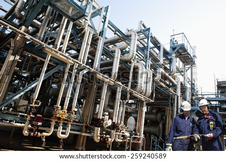 oil workers and the main refinery fuel station supplying shipping industry - stock photo