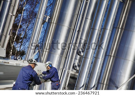 oil workers with giant pipelines, power industry - stock photo