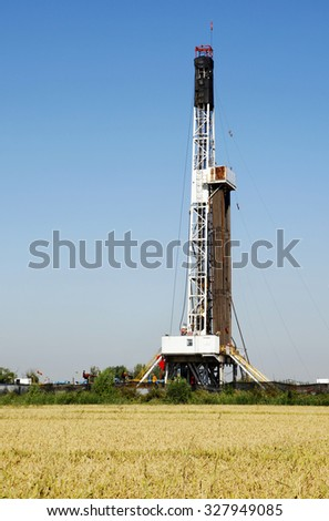 Oilfield derrick and paddy fields - stock photo