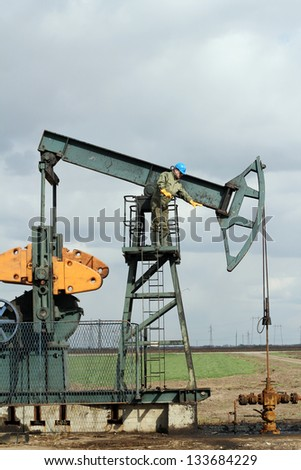 oilfield with worker and pump jack - stock photo