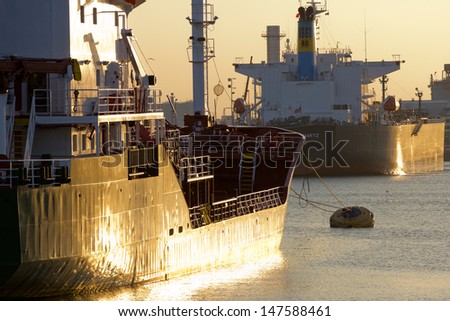 Oiltanker docking in a harbour during sunset - stock photo