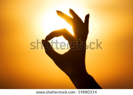 Ok hand sign silhouette. On bright sun background. - stock photo