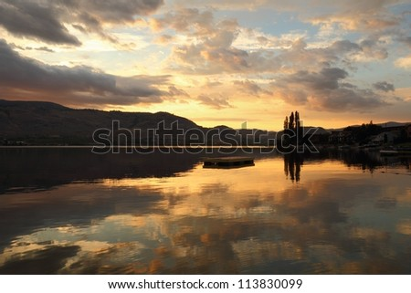 Okanagan, Osoyoos Lake Dawn. A quiet morning on Osoyoos Lake, British Columbia, Canada. The first light of the morning lights up the sky and reflects in the still lake. - stock photo