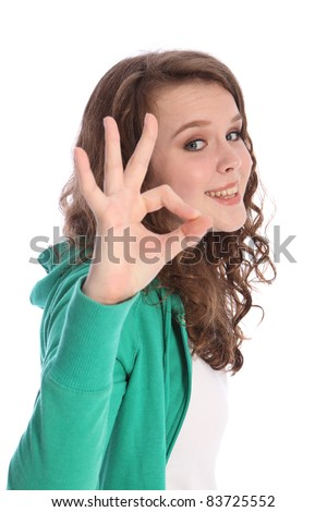 Okay hand sign for success by happy pretty teenager school girl with long brown hair. Girl has blue eyes and a big beautiful smile.
