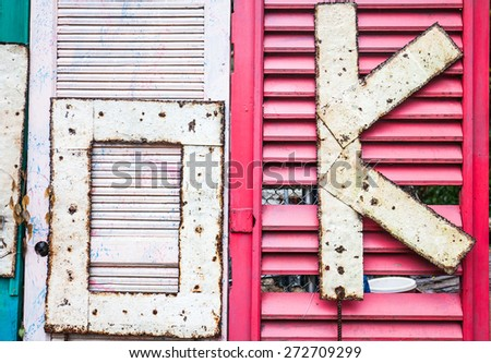 okay sign made by rusty metal on old door background - stock photo