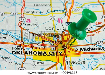 Oklahoma City highlighted with push pin on atlas or map - stock photo