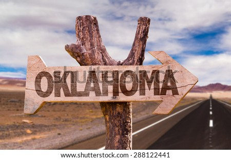 Oklahoma wooden sign with desert road background - stock photo