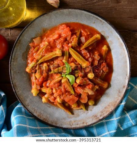 Okra dish with tomatoes (Traditional greek, romanian, bulgarian and turkish dish) - stock photo