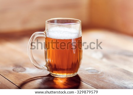Oktoberfest background. Glass of beer on wooden background.  Mug of beer festival, template background. Craft beer.