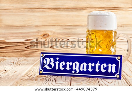 Oktoberfest Biergarten, or Beer Garden, concept with a blue German text sign propped against a glass mug of golden frothy beer on a wooden background with copy space - stock photo