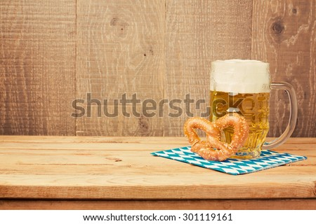 Oktoberfest german beer festival  background with beer glass and pretzel on wooden table - stock photo