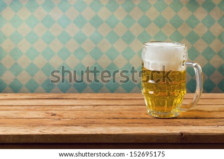 Oktoberfest holiday. Beer on wooden table over retro wallpaper with bavarian flag pattern