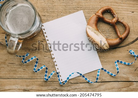 Oktoberfest: Masskrug of beer, Pretzels and bavarian streamer on rustic wooden table with empty piece of paper - stock photo