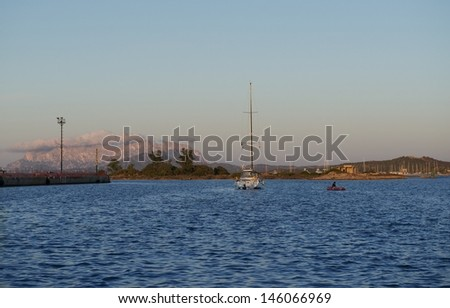 Olbia,Sardinia,Yacht and small boat sailing towards sunset in dark background with the mountains,sunset background, yacht in the sunset,water sport, yacht sailing in sunset,Italy, holiday in the sea