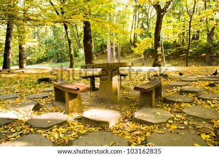 old a chair and benches (are made of a stone and a tree), located in park. autumn. - stock photo
