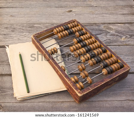 Old abacus, pencil and notepad on a wooden table - stock photo