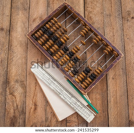 Old abacus, the paper with a pencil and sliding rule on a wooden table - stock photo