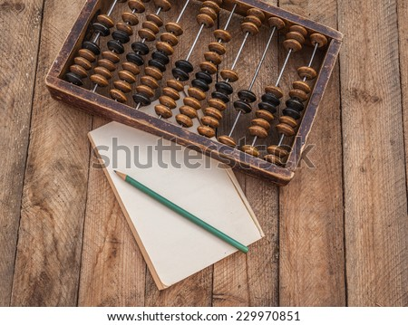 Old abacus, the paper with a pencil on a wooden table - stock photo