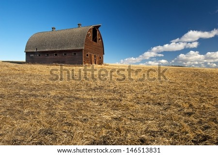 Old abandoned barn on  hilltop Harvested grain field in foreground - stock photo