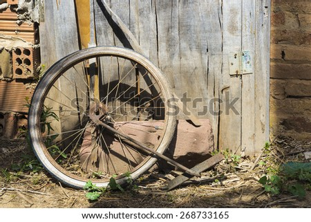Old abandoned bicycle wheel in a cottage - stock photo