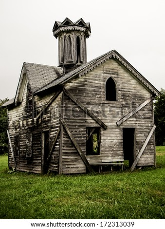Old Abandoned Building 2. The facade of a small abandoned church or similar historic structure in a rural setting. - stock photo