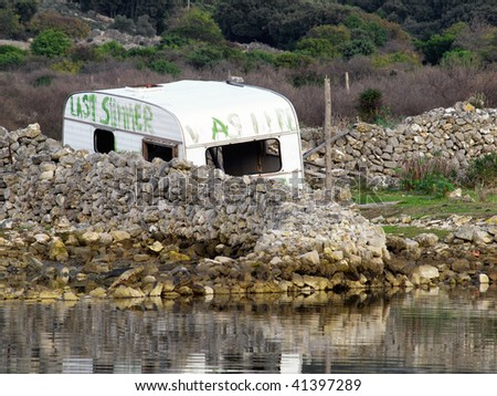 Old abandoned camping caravan somewhere in nature. - stock photo