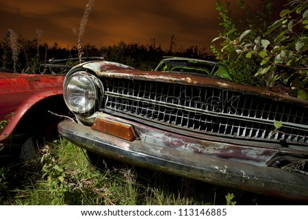 old abandoned car in a junkyard at night light painted - stock photo