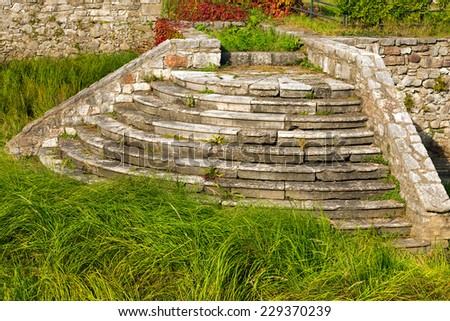 Old abandoned circular staircase with white stone steps in an uncultivated garden - stock photo