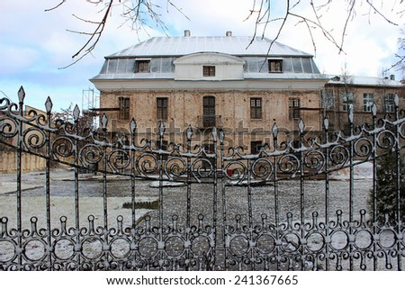 Old abandoned cottage. A snow-covered building behind wrought-iron gates. The urban landscape. - stock photo