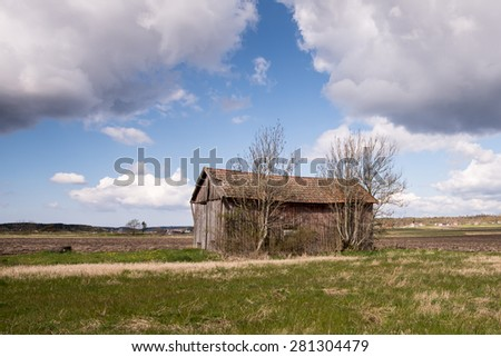 Old abandoned country barn with clouds