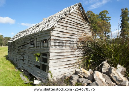 Old abandoned damaged farm hut in countryside on green grass field at sunny day, blue sky as background, copy space. - stock photo