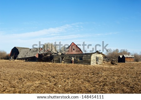 Old abandoned farm. Collapsed log house, old barns and old granaries.  Image taken in early spring - stock photo