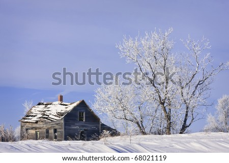 Old abandoned farm house in a frosty winter wonderland - stock photo