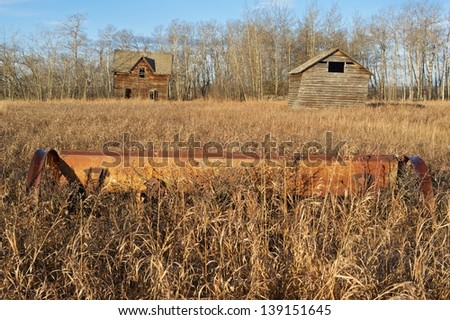 old abandoned farm with house,barn and old machine in foreground - stock photo