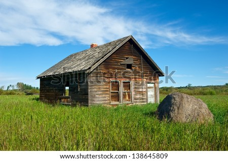 Old abandoned farmhouse in grassy field.  Rotting hay bale in front.  A rotting old log house in the left background
