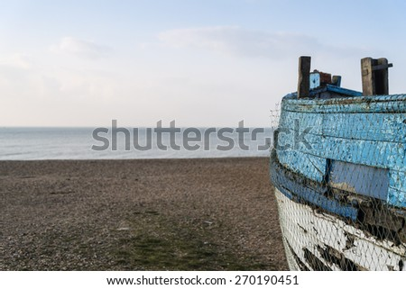 Old abandoned fishing boat on beach with shallow depth of field - stock photo