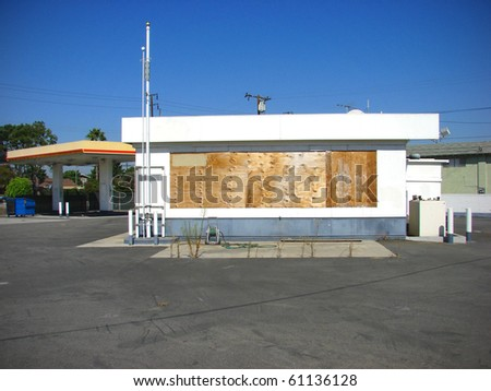 old abandoned gas station boarded up with plywood