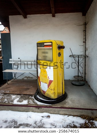 Old abandoned gas station with yellow pump - stock photo