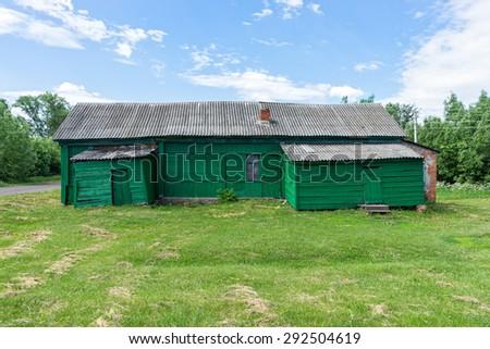 Old abandoned green wooden house on sunny meadow. Staroyurievo village, Tambovsky region, Russia.  - stock photo