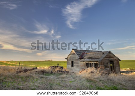old abandoned house and farming machinery on Colorado prairie with green fields in background - stock photo
