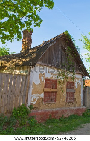 old abandoned house covered in vegetation - stock photo