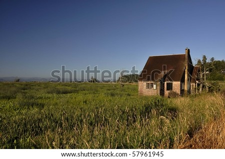 Old abandoned house in marsh at sunset
