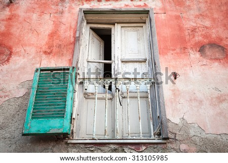 Old abandoned house wall with white wooden balcony door and green shutters, Gaeta, Italy - stock photo