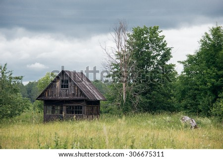 Old abandoned hut at the meadow near forest - stock photo