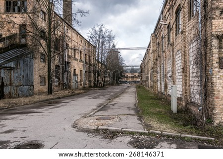 Old abandoned industrial street view with brick facades - stock photo