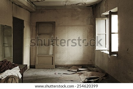 Old abandoned interiors; nobody in the photo, nice light effect from the window on the right. - stock photo