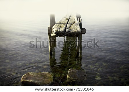 old abandoned jetty in the fog - stock photo