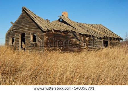 Old abandoned log cabin in dry dead grass in fall - stock photo