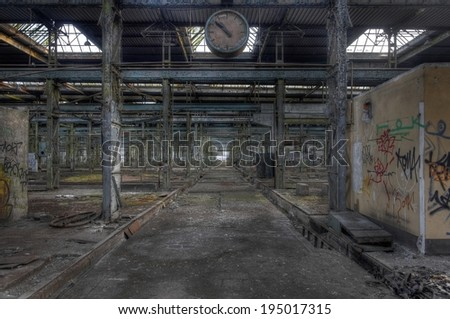 Old abandoned production hall with a clock - stock photo