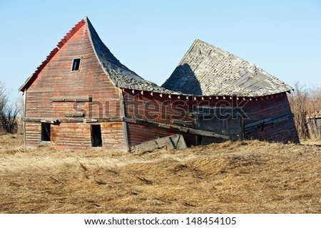 Old abandoned red barn with the roof collapsing in  - stock photo